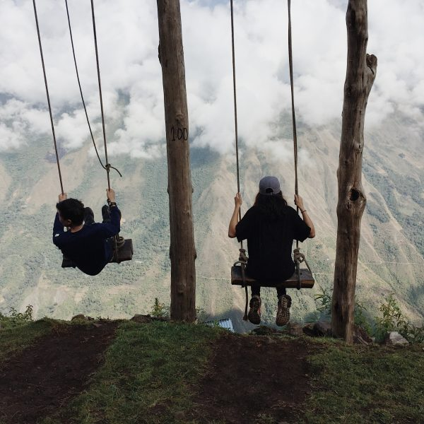 sitting on swings at edge of a moutain peru